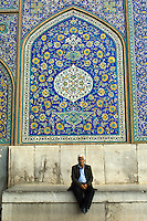 An old man sits below the fabulous Safavid era mosaics in the entrance portal to the Sheikh Lotfollah Mosque in Isfahan, Iran.