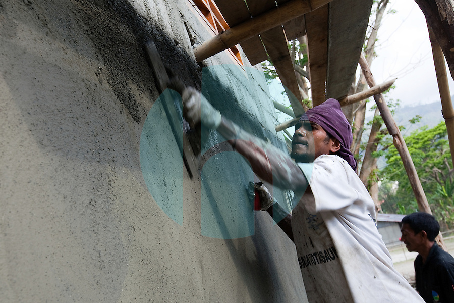 A man puts the finishing touches on the outside of a new building in the mountain town of Laclubar, Timor-Leste on Tuesday, Oct. 18th, 2011.  Photographer: Daniel J. Groshong/The Hummingfish Foundation