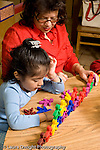 Education Preschool 3-5 year olds female teacher working with girl on patterns, colors, and counting vertical