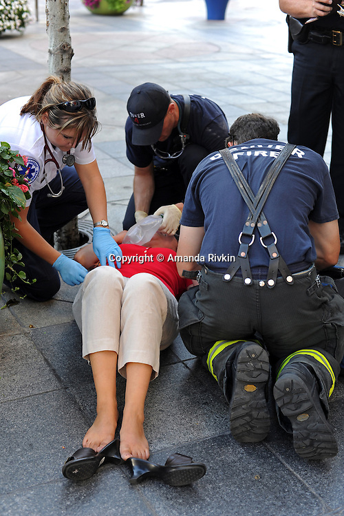 First aid responders attend to a woman passed out from lack of oxygen on the 16th Street Mall in downtown Denver, Colorado on August 21, 2008.  Four days before the Democratic National Convention kicks off at the nearby Pepsi Center, emergency workers, police, and first responders are on call in the event of accidents and emergencies.