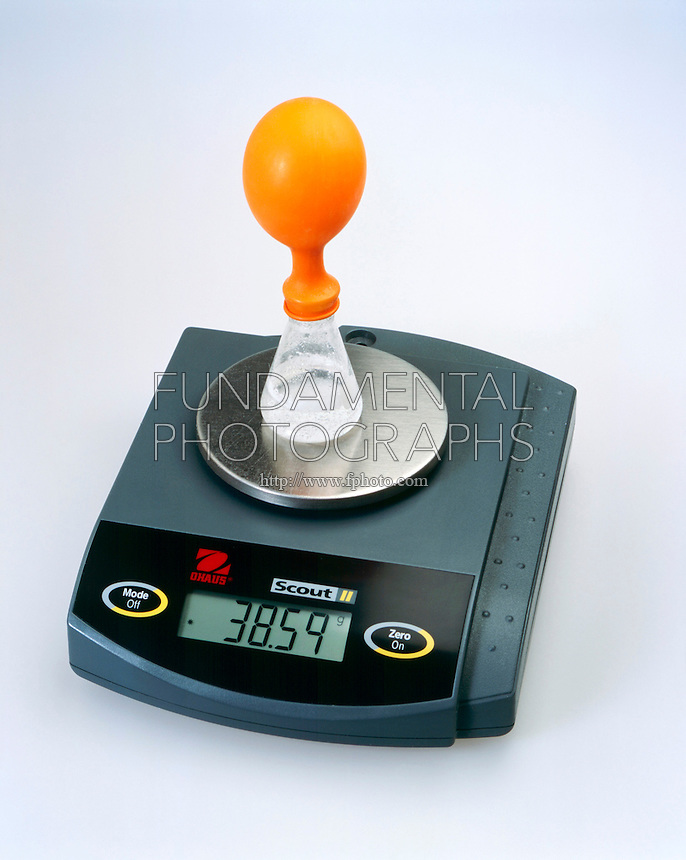 LAW OF CONSERVATION OF MASS <br /> (4 of 6)<br /> CO2 Reaction in Closed System with Orange Balloon<br /> When the crushed alka-seltzer is emptied into the water, CO2 gas is released which inflates the balloon. Mass changes to 38.59g. Because gas is lifting balloon off the balance.