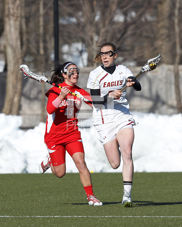 Boston College defender Claire Blohm (26) brings the ball forward as Boston University attacker Danielle Etrasco (13) closes..Boston College (white) defeated Boston University (red), 12-9, on the Newton Campus Lacrosse Field at Boston College, on March 20, 2013.