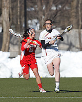 Boston College defender Claire Blohm (26) brings the ball forward as Boston University attacker Danielle Etrasco (13) closes..Boston College (white) defeated Boston University (red), 12-9, on the Newton Campus Lacrosse Field at Boston College, on March 20, 2013.