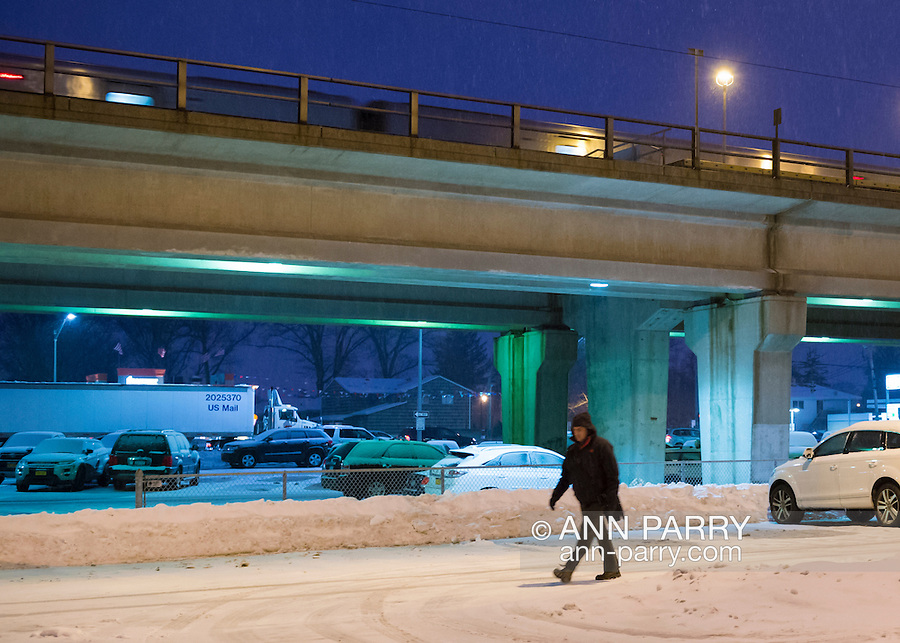 Merrick, New York, USA. March 3, 2015. During peak of evening commute, snow falls at Merrick Long Island Rail Road LIRR train station, as a man walks through the snowy parking lot with the elevated train platform behind. The area is under a Winter Weather Advisory, and a Winter Storm Watch for hazardous conditions is in effect from Wednesday night to Thursday night in Long Island, New York City and other nearby areas of the northeast