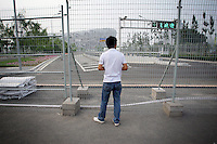 """CHINA. Beijing. A man peers through a fence, trying to catch a glimpse of the new Olympic park. In recent years construction has boomed in Beijing as a result of the country's widespread economic growth and the awarding of the 2008 Summer Olympics to the city. For Beijing's residents however, it seems as their city is continually under construction with old neighborhoods regularly being razed and new apartments, office blocks and sports venues appearing in their place. A new Beijing has been promised to the people to act as a showcase to the world for the 'new' China. Beijing's residents have been waiting for this promised change for years and are still waiting, asking the question """"Where's the new Beijing?!"""". 2008."""
