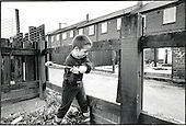 An 8 year-old boy smashes a fence for bonfire wood in a street of vandalised houses in the ex-mining village of Grimethorpe in South Yorkshire.