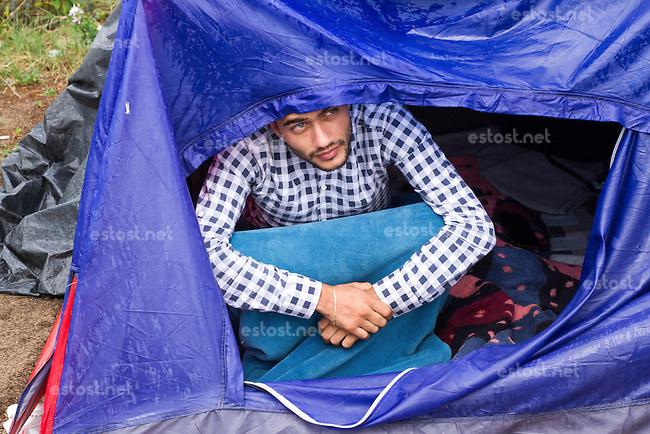 SERBIEN, 08.2016, Kelebija. Internationale Fluechtlingskrise: An der mit Zaeunen abgesperrten ungarischen Grenze stauen sich Fluechtlinge und Migranten. Sie bitten meist vergebens um Einlass in die  Asyl- und Transitzonen (blaue Container). So haben sich auf serbischer Seite provisorische Lager mit sehr schlechten Bedingungen gebildet. | International refugee crisis: Refugees and migrants have been piling up at the fenced-off Hungarian border. They are waiting for entrance into the asylum and transit zones (blue containers), mostly in vain. Thus provisional camps have emerged on the Serbian side with very bad conditions. In the picture Elvis Kasu.<br /> © Szilard Vörös/EST&OST