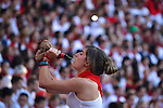 A woman drinks before the second bull run of the San Fermín Festival in Pamplona, northern Spain, on July 8, 2013, in Pamplona, northern Spain. © PEDRO ARMESTRE