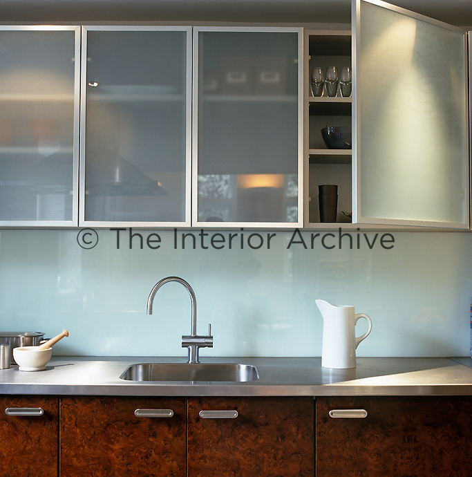 This contemporary kitchen is a combination of wood, stainless steel and frosted glass