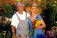 Mature age couple embrace in their country flower garden.