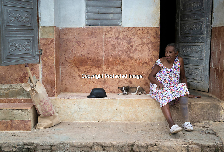27/07/18<br /> <br /> A elderly woman with false leg sits in a doorway with puppy and motorcycle helmet, Trinidad, Cuba.<br /> <br /> All Rights Reserved, F Stop Press Ltd. (0)1335 344240 +44 (0)7765 242650  www.fstoppress.com rod@fstoppress.com