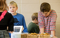 STAFF PHOTO JASON IVESTER --12/18/2014--<br /> Graham Hardin (left) and Strael (cq) Wolfe (cq) help customers on Thursday, Dec. 18, 2014, inside Sugar Creek Elementary School in Bentonville. Third-graders at the school sold hot chocolate and snacks to students and staff to raise money for the Northwest Arkansas Children's Shelter.