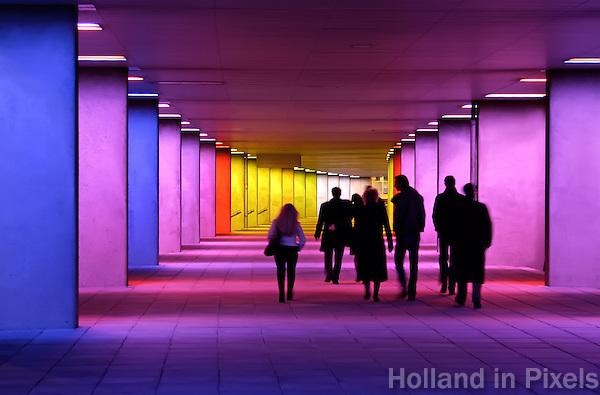 Mensen lopen door de verlichte Arcade van NAI Architectuur instituut in Rotterdam