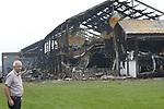 Foto: VidiPhoto<br /> <br /> ERICHEM &ndash; De brandweer is vrijdag nog lange tijd bezig geweest met het nablussen van de enorme brand in de stallen van De Knorhof aan de Erichemsewal in Erichem, bij Tiel. De brand is volgens de brandweer ontstaan in een stal achter het woonhuis. De oorzaak is nog niet bekend. Door niet ge&iuml;mpregneerde isolatiepanelen en de zogenoemde luchtwassers, die stank in de omgeving tegengaan, verspreidde de brand zich razendsnel door alle stallen. Binnen een half uur was het vuur verspreid door het hele complex. Daarbij kwamen 16.000 varkens om. Het bedrijf heeft vergunning voor 20.000 varkens. Het enorme complex telt ongeveer 120 bij 120 meter. Bij de brand is asbest in de directe omgeving vrijgekomen. Een extern bedrijf brengt het verspreidingsgebied in kaart. Verderop in het dorp zijn roetdeeltjes neergedaald. De brand in Erichem is de grootste varkensbrand ooit in ons land. Foto: Werknemer Piet Stout voor de afgebrande varkensstallen in Erichem. Hij werkt er 8,5 jaar en is tevens plaatsvervangend bedrijfsleider. Zijn huis op enkele meters afstand van de stallen kon nog gered worden.