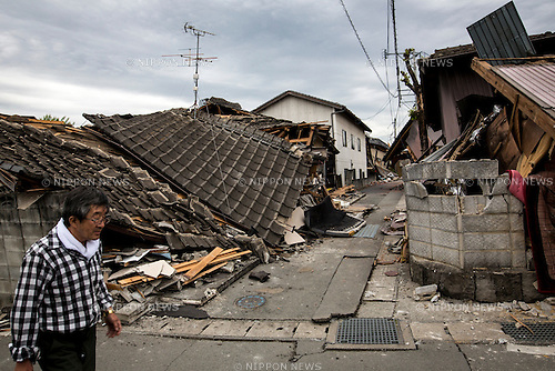 KUMAMOTO, JAPAN - APRIL 16: A man walks past the wreckage of houses on April 16, 2016 in the streets of Mashiki, Kumamoto Prefecture, Japan. The area was severely hit by a magnitude-6.5 quake Thursday night and followed by magnitude-7.3 quake on Saturday early morning on April 16, 2016 in Kumamoto prefecture, Japan.(Photo by Richard A. de Guzman/AFLO)