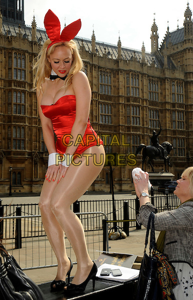 MODEL.Missimo.com waves goodbye to the Playboys with their very own Bunnies at Westminster, Houses of Commons, London, England..Just in time for the election year, 2010 marks 50 years since the world was first introduced to the Playboy Bunny and the now legendary bunny costume. As part of the celebrations missimo.com, the online branded clothing retailer will launch a global exclusive: The first official Playboy Bunny outfit - complete with ears and tail..April 12th, 2010.full length strapless red ears cleavage leotard black peep toe shoes looking down.CAP/IA.©Ian Allis/Capital Pictures.