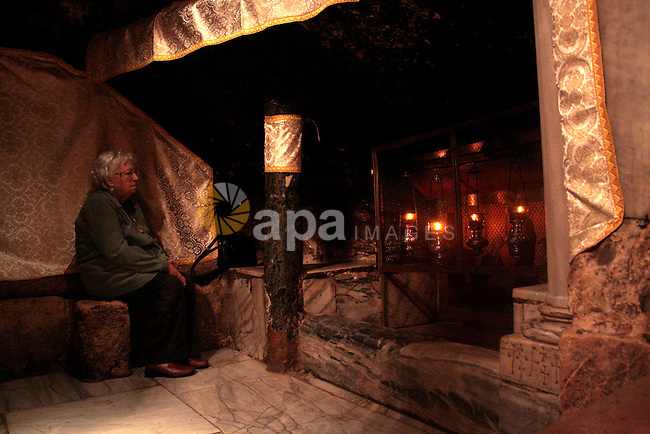 A Christian pilgrim prays in the Grotto, the alleged birthplace of Jesus Christ, in the Church of the Nativity during Sunday mass, April 24 2011.Photo by Najeh Hashlamoun..