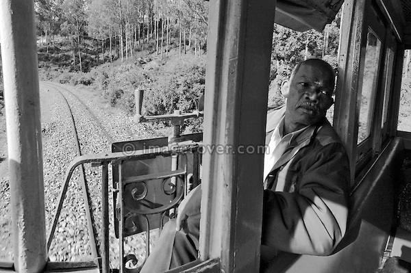 Train crew of the Nilgiri Mountain Railway (steam train) during a journey through the Nilgiri Mountains from Ooty to Coonoor.  India, Tamil Nadu 2005. --- Info: The Nilgiri Mountain Railway (NMR) is the only rack railway in India and connects the town of Mettupalayam with the hill station of Udagamandalam (Ooty), in the Nilgiri Hills of southern India. The construction of the 46km long meter-gauge singletrack railway in Tamil Nadu State was first proposed in 1854, but due to the difficulty of the mountainous location, the work only started in 1891 and was completed in 1908. This railway, scaling an elevation of 326m to 2,203m and still in use today, represented the latest technology of the time. In July 2005, UNESCO added the NMR as an extension to the World Heritage Site of Darjeeling Himalayan Railway.