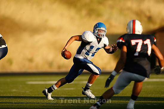 Provo - PG quarterback Dallas Lloyd scrambles. Timpview's Tevia Tolutau at right. Timpview vs. Pleasant Grove high school football Friday, August 21 2009...