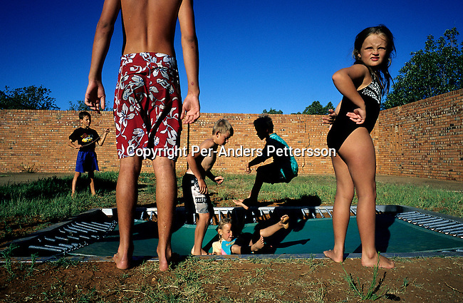 Unidentified children play on a trampoline at a playground in Orania, on December 13, 2003 in Orania, in the Northern Cape Province, South Africa. The village was founded in 1991 and bought by descendants of Hendrik Verwoerd, the architect of Apartheid. It's a private white only town and about 600 Afrikaners lives in the village where they celebrate their culture and keep traditions alive. They have chosen not to live in today's South Africa; a country ran by a black government since 1994. (Photo by: Per-Anders Pettersson) .....