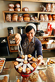 USA, Venice Beach, a barista grabbing pastries for a customer at 3 Square Bakery located on Abbot Kinney in Venice Beach