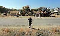 Pictured: A forensics officer takes pictures as diggers work to clear the new site of the search, where rubble was deposited from the farmhouse where Ben Needham disappeared from in Kos, Greece. Thursday 06 October 2016<br />