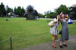 """July 18, 2014, Tokyo, Japan - People take themselves pictures in front of the 6.6 meter model of the new Godzilla at Tokyo Midtown on July 18, 2014, Tokyo. The statue is a 1/7 scale reproduction of the 180 meters tall Hollywood film version of """"GODZILLA"""".  Godzilla and its footprints will be displayed from July 18 to August 31 during which time it will perform a special show using mist, light and sound effects every 30 minutes between 19:00 to 21:00. (Photo by Rodrigo Reyes Marin/AFLO)"""