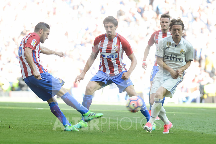 Real Madrid's Luka Modric and Atletico de Madrid's Koke Resurrecci&oacute;n and Stefan Savic during La Liga match between Real Madrid and Atletico de Madrid at Santiago Bernabeu Stadium in Madrid, April 08, 2017. Spain.<br /> (ALTERPHOTOS/BorjaB.Hojas)