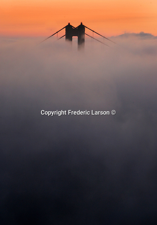 The North tower of the Golden Gate Bridge was visible through a blanket of fog just before sunrise from the Marin Headlands, California.