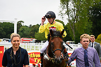 Winner of The Bathwick Tyres EBF Novice Stakes, Beringer ridden by Finley Marsh and trained by Alan King is led into the winners enclosure during Ladies Evening Racing at Salisbury Racecourse on 15th July 2017