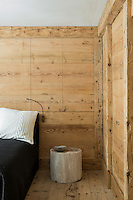A contemporary bedroom in a traditional style wood panelled chalet with minimal furnishings and a log used as a bedside table