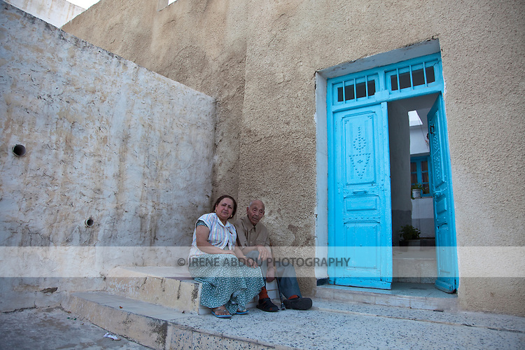 Fathia Wijlini Hatlab sits with her father in front of their home in El Kef.  El Kef, the capital of Western Tunisia, is an interesting town speckled with winding alleys, whitewashed walls, and sea blue wooden doors decorated in traditional Tunisian fashion.