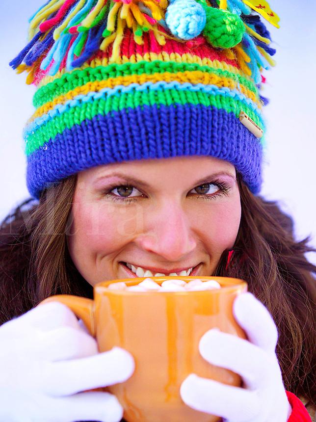 Woman in ski cap with mug of hot cocoa