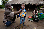 "Joseph Dzongololo washes the face of his son Matthew, 4, in Chidyamanga, a village in southern Malawi that has been hard hit by drought in recent years, leading to chronic food insecurity, especially during the ""hunger season,"" when farmers are waiting for the harvest."