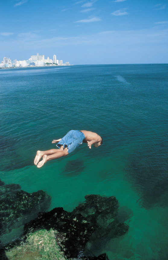 A boy dives off the edge of the malecon. Street scenes from Havana, Cuba 9-02