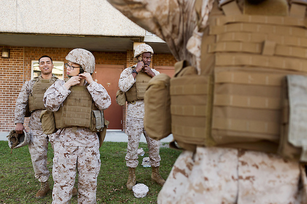 October 22, 2014. Camp LeJeune, North Carolina.<br />  LCpl. Karla Cardenas, age 20, 2nd from left, buckles her helmet before taking part in patrol training for the 3rd Platoon of the Ground Combat Element Integrated Task Force. Marines in 3rd Platoon of the GCEITF are all considered provisional infantrymen as they have not been to the School of Infantry (SOI) previous to volunteering for the GCEITF.<br />  The Ground Combat Element Integrated Task Force is a battalion level unit created in an effort to assess Marines in a series of physical and medical tests to establish baseline standards as the Corps analyze the best way to possibly integrate female Marines into combat arms occupational specialities, such as infantry personnel, for which they were previously not eligible. The unit will be comprised of approx. 650 Marines in total, with about 400 of those being volunteers, both male and female. <br />  Jeremy M. Lange for the Wall Street Journal<br /> COED