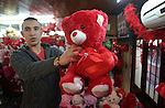 Palestinian vendors display flowers red teddy bears and pillows on Valentine's day in the West Bank city of Ramallah, on February 14, 2016. Valentine's Day is increasingly popular in the region as people have taken up the custom of giving flowers, cards, chocolates and gifts to sweethearts to celebrate the occasion. Photo by Shadi Hatem