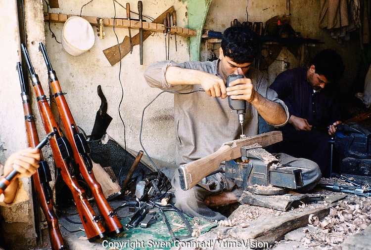 A men making Butt's for new made rifles. Darra town in Pakistan clandestinely provides arms to more than eight Central Asian countries.