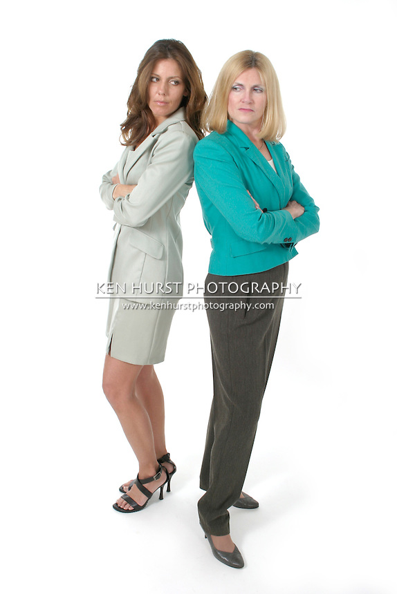 Attractive and beautiful two business woman team standing back to back with serious, glaring expressions. Shot on white.