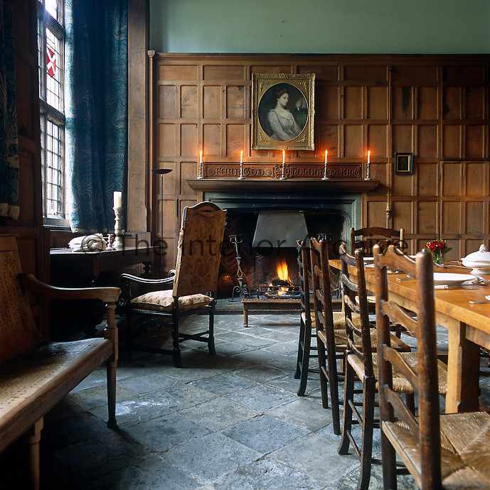 This panelled country dining room has an offset fireplace and an original stone-flagged floor