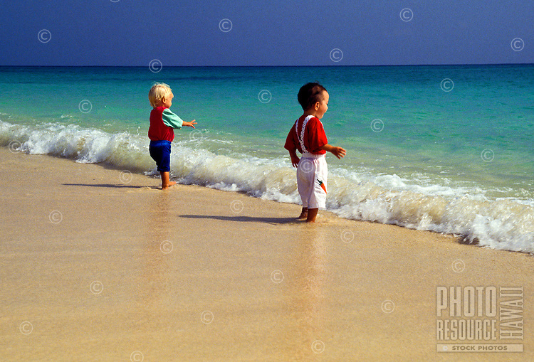 Two small boys dressed in shorts and t-shirts, stand by the waters edge at world famous Lanikai Beach on windward Oahu.