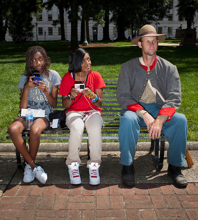 Zhane Perkins, left, and Shannon Burns, share a bench with Civil War re-enactor Bobby Allen, from Asheboro, NC, on the grounds of the Old State Capitol in Raleigh, Saturday, May 21, 2011 -- 150 years after North Carolina officially seceded from the Union.