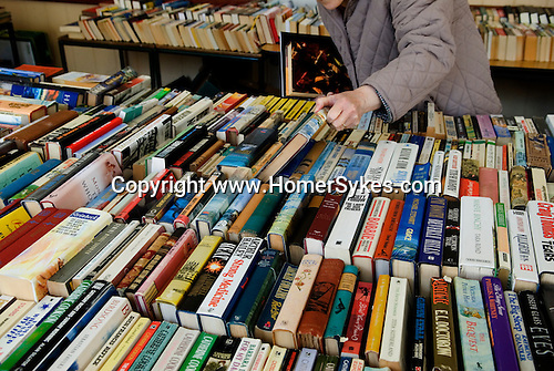 Old age pensioner looks through a selection of second hand books, shop sale Petworth, West Sussex. England.