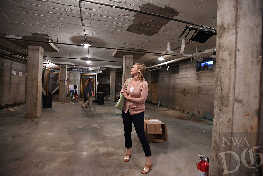 NWA Democrat-Gazette/J.T. WAMPLER  Kaitlyn Fondano, construction manager with Specialized Real Estate Group, looks around the basement Thursday August 8, 2019 at the former Farmers Cooperative building on Martin Luther King Jr. Blvd. <br /><br />Specialized Real Estate Group bought the property this year and plans to put in more than 200 apartments and renovate the existing properties for a mix of restaurants, entertainment, office and retail space.
