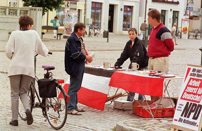 Vor allem mit Westkadern fuerte die rechtsextremistische NPD in Mecklenburg-Vorpommern einen sogenannten Schwerpunktwahlkampf zur Landtagswahlt 1998. Die Parteifuehrung rechnete sich in Mecklenburg-Vorpommern beste Chancen fuer Landtagsmandate aus. Sie blieb jedoch unter der Fuenf-Prozent-Huerde. Parteimitglieder gaben zu, da&szlig; es nur um die Wahlkampfkostenrueckerstattung ging.<br /> Hier: Wahlkampfhelfer am Wahlinformationsstand auf dem Marktplatz von Stavenhagen im Gespraech mit einem sympathisierenden Passanten.<br /> 19.08.1998, Stavenhagen, Mecklenburg-Vorpommern<br /> Copyright: Christian-Ditsch.de<br /> [Inhaltsveraendernde Manipulation des Fotos nur nach ausdruecklicher Genehmigung des Fotografen. Vereinbarungen ueber Abtretung von Persoenlichkeitsrechten/Model Release der abgebildeten Person/Personen liegen nicht vor. NO MODEL RELEASE! Nur fuer Redaktionelle Zwecke. Don't publish without copyright Christian-Ditsch.de, Veroeffentlichung nur mit Fotografennennung, sowie gegen Honorar, MwSt. und Beleg. Konto: I N G - D i B a, IBAN DE58500105175400192269, BIC INGDDEFFXXX, Kontakt: post@christian-ditsch.de<br /> Bei der Bearbeitung der Dateiinformationen darf die Urheberkennzeichnung in den EXIF- und  IPTC-Daten nicht entfernt werden, diese sind in digitalen Medien nach &sect;95c UrhG rechtlich geschuetzt. Der Urhebervermerk wird gemaess &sect;13 UrhG verlangt.]
