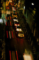 Cars travelling along a street during a rainy night.
