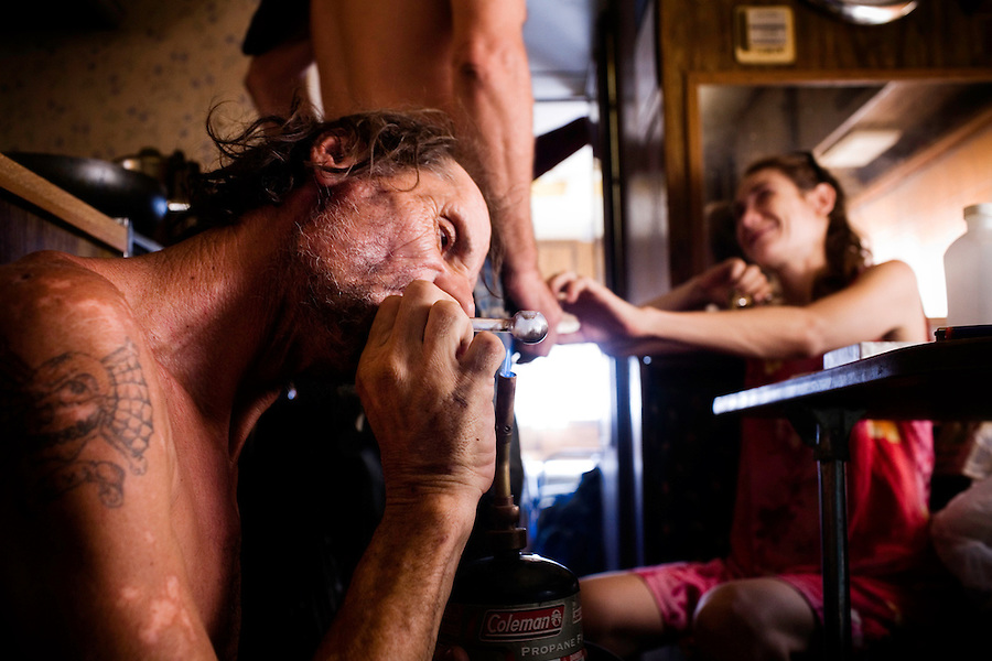 """Niland, California, July, 12, 2008 -  Jerry Jones takes a hit from his pipe, while friend Ben Morofsky teases his wife Moriah by hiding her pipe in his pants. Jerry says that he uses the drugs to escape the pain of his wife dying. Adding, """"It hurts, man. I mean, sitting here watching your wife dying and not being able to do nothing. It just kills me."""""""