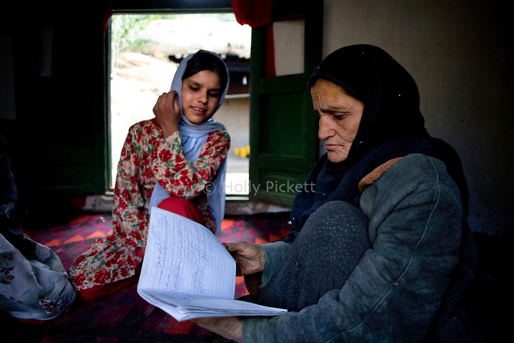 Nagmi, right, a resident, wife and mother in Farghamanch village, looks through a practice notebook while 14-year-old Madida looks on in Farghamanch, Jurm district, Badakhshan province, Afghanistan, Friday afternoon, Oct. 23, 2009. Nagmi has been participating in an afternoon literacy program at the new school. As the Obama Administration seeks the formula for turning the tide of the war in Afghanistan, some aid organizations are advocating the National Solidarity Programme, a community-based development program that has made progress in some districts, setting up local councils that propose much-needed projects such as schools, drinking water facilities and roads.