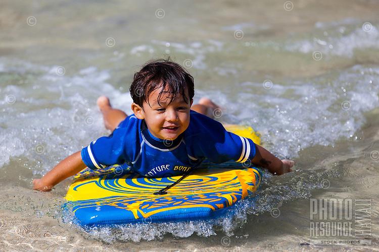 A young local Hawaiian boy bodyboards at the beach on O'ahu.