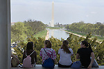 Four young women visiting Washington D.C. take a break to sit on the Lincoln monument and look toward the Washington momument and the capitol beyond.